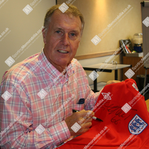 Sir Geoff Hurst signing autograph on 1966 England shirt