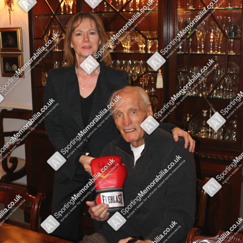 Sir Henry Cooper signing boxing gloves with Freda Baker, Director of A1 Sporting Memorabilia