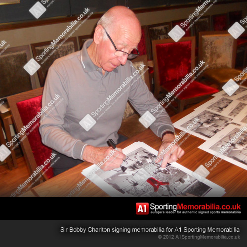 Sir Bobby Charlton signing memorabilia for A1 Sporting Memorabilia